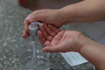 mujer colocándose alcohol en gel en las manos con barbijo