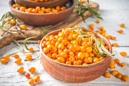 Sea buckthorn berries in small organic wooden bowl, with sea buckthorn branches on white wooden desk background
