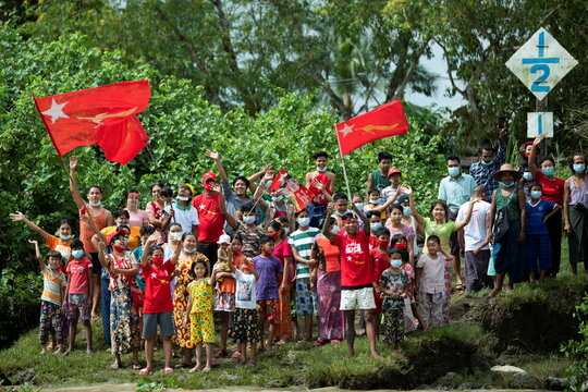 Supporters of the National League for Democracy party greet to a boat rally ahead of a November 8 general election, amid the coronavirus disease spread in the Yangon river, Myanmar,