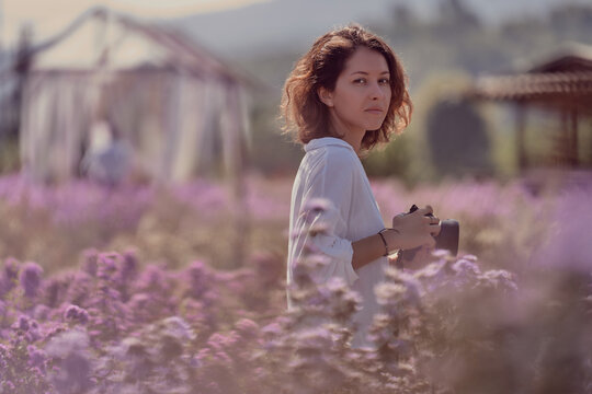 young cute woman professional photographer on a flower field in summer