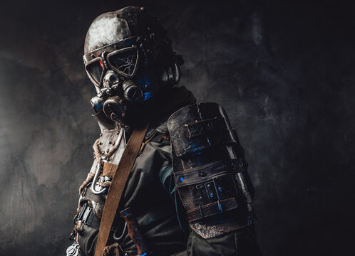 Epidemic and apocalyptic survivor dressed in his custom dark armour and gas mask with broken glass in dark background.