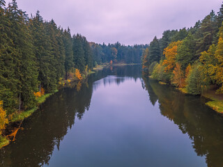 Drone view of a beautiful autumn forest landscape with a river on a cloudy day with a reflection in the river. Beautiful autumn landscape