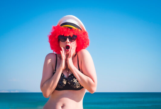 Close up portrait of a crazy middle aged lady in red wig, black shiny swimsuit shocked against the sky and sea. Surprised and scared Beauty cute wotan in a navy cap on a tropical resort.