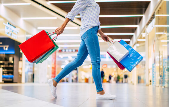 Cropped photo of cute glamour woman with bright colorful shopping bags while she walking on the mall