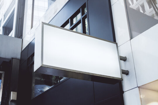 White rectangular sign with blank space for your logo on the wall of a modern business center, mockup