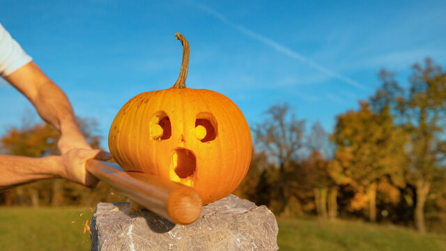 CLOSE UP: Halloween pumpkin with shocked face gets smashed with wooden bat