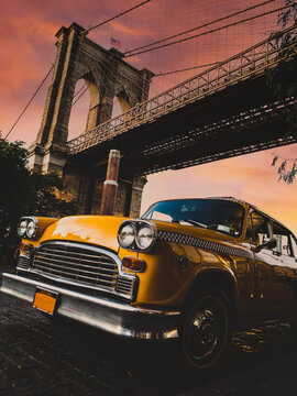 Vintage yellow taxi cab in New York under the Brooklyn Bridge with a colorful sky during sunset