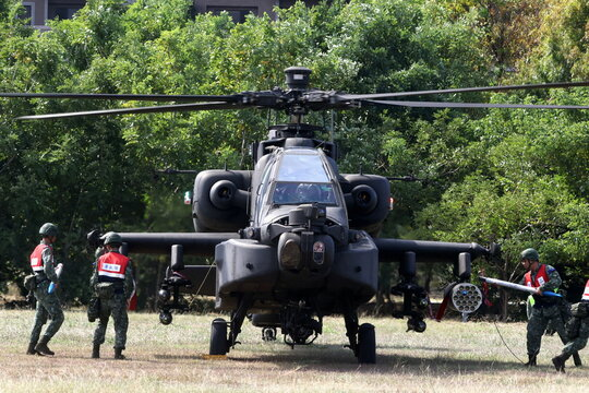 Soldiers load training rockets into a pod on an AH-64E Apache attack helicopter during 'Combat Readiness Week' drills in Hsinchu, Taiwan