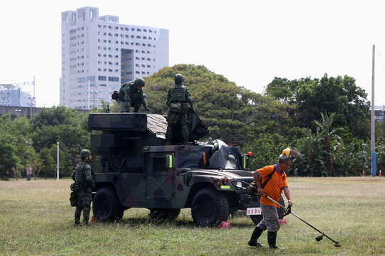 A staff trims grass while soldiers work on a military vehicle after 'Combat Readiness Week' drills in Hsinchu