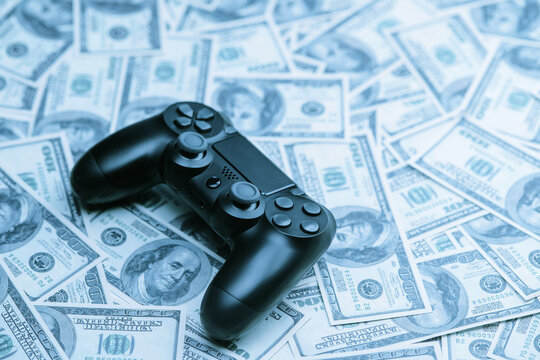 Concept of gaming addiction. Close up photo of gamepad on the money background.