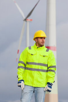 Smiling young engineer with hard hat and protective clothing in front of blurred wind turbines