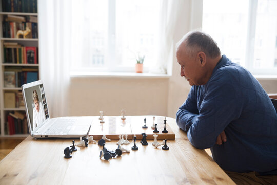 Senior old man playing chess game on chess board, online game with friend, video call due to social distancing at home