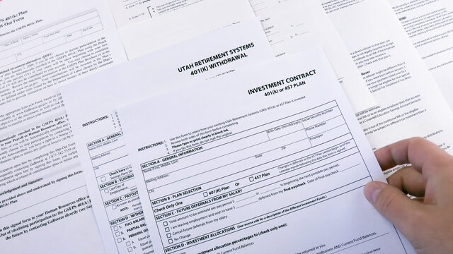 Conceptual composition. Pension savings. Man puts on the table Blank form Investment contract 401 k or 457 plan, blank form Utah retirement system 401 k and Personal 401k plan. Close-up
