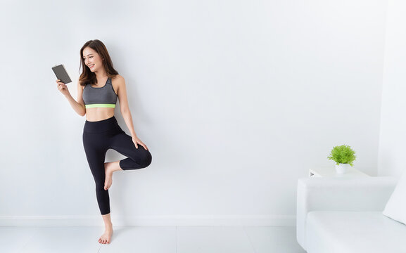 Portrait of young beautiful asian korean woman warm up exercise workout yoga position in white living room. Sporty girl reading book relax at minimal home health care lifestyle knowledge concept