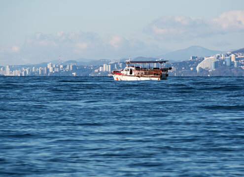 Passenger ship or steam boat on sea voyage at Sochi coastline background at sunny day