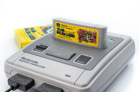 Fukuoka, Japan - june 22, 2019 : the famous nintendo 1990's hit super mario world cartridge plug in the original Nintendo Super Famicom