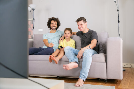 Happy gay fathers and son watching funny TV show at home, sitting on couch in living room, smiling and laughing. Family and home entertainment concept