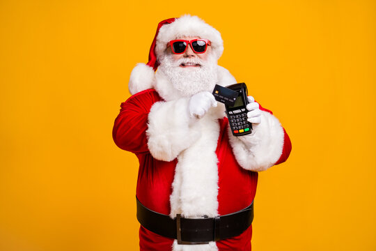 Portrait of his he nice attractive cheerful fat overweight Santa using wireless bank card digital terminal paypass system isolated bright vivid shine vibrant yellow color background