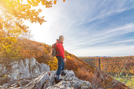 Senior male hiker standing on a cliff ledge and looking at a colourful hilly autumn landscape in the Swabian Jura