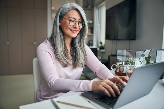 Cheerful woman in glasses working on laptop at home