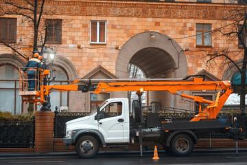 Aerial platform truck, repair and maintenance of street lamps, electricians replace led light bulb. Workers in cherry picker repairing street lights. Men working in lift bucket Fotomurales