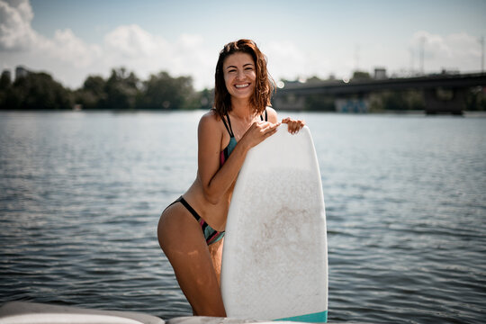 happy beautiful young woman in bright bikini with surf board with her hands