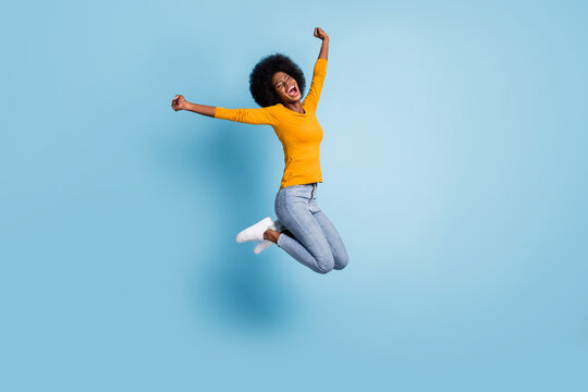 Photo portrait full body of excited girl celebrating jumping up isolated on pastel blue colored background