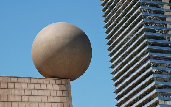 The Esfera (sphere) sculpture by architect Frank Gehry on a rooftop at Port Olimpic in Barcelona, Spain on April 17, 2018. The Mapfre Tower skyscraper is in the background.