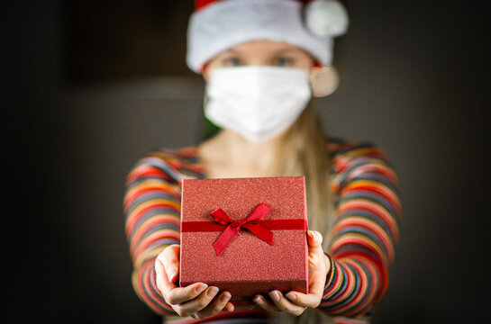 Young blonde caucasian girl in Santa hat and striped jumper , with protective mask on face, holding, giving a gift, present to the camera.  Coronavirus lockdown Christmas concept.