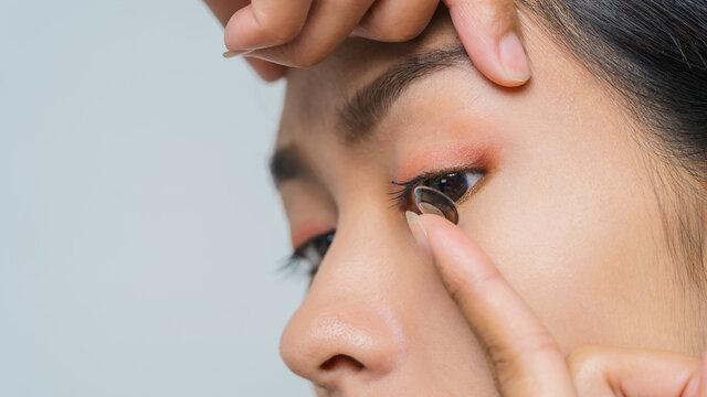 Close-up young Asian woman wearing contact lens, macro shot.