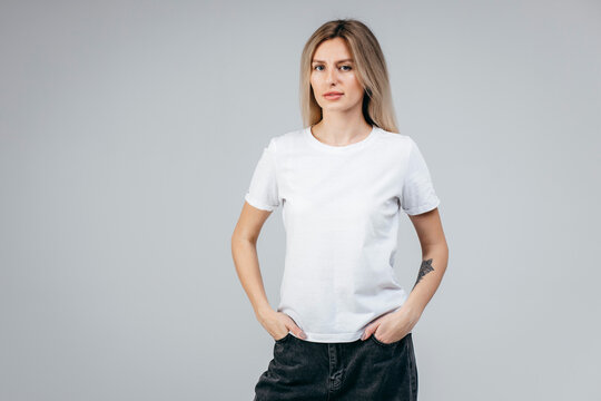 Stylish blonde girl wearing white t-shirt posing in studio