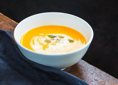 Pumpkin and vegetables cream soup dark background copy space.
