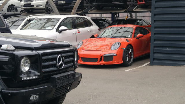 Moscow. Autumn 2018. Orange Porsche 911 GT3 RS On the parking, Racing supercar front side view and mercedes benz g class grill at foreground