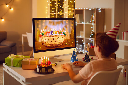 Little boy having online birthday party and looking at beautiful cake on computer screen