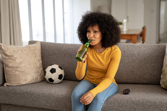 Woman drinking beer while watching sports on TV at home
