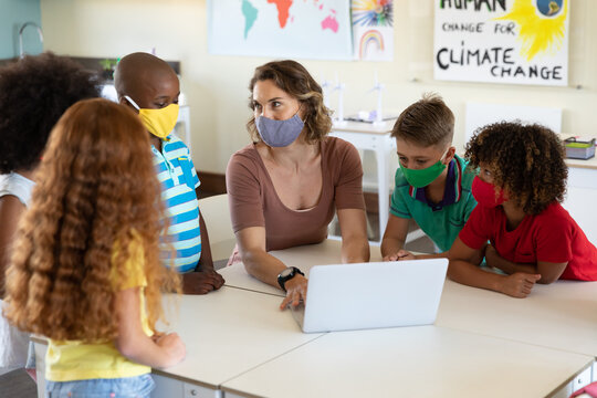 Female teacher wearing face mask using laptop to teach students in class