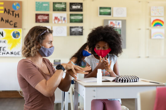 Female teacher wearing face mask helping a girl to sanitize her hands in class
