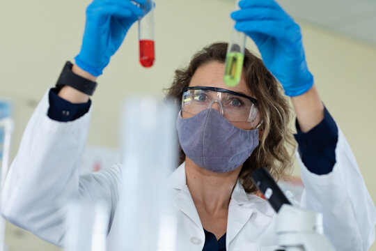 Female teacher wearing face mask and protective glasses holding two test tubes in laboratory