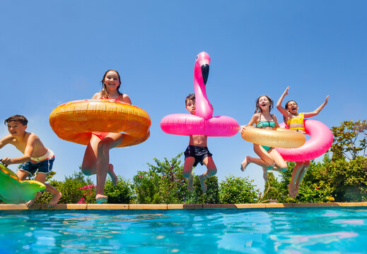Group of happy little kids dive in water with inflatable toys flamingo doughnut jump into the swimming pool