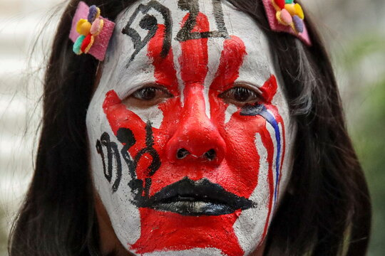 """A protester with her face painted with words """"Slap me"""" takes part in a protest against the government and to reform monarchy in Bangkok"""