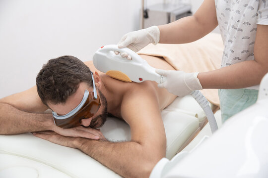 Young man getting back and shoulder laser hair removal epilation. IPL treatment in cosmetic beauty salon