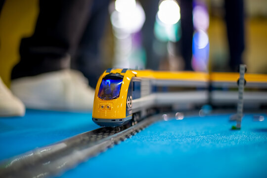 Moscow, Russia - October 04, 2019: toy yellow electric lego train rides on toy rails on a blue floor. legs in white sneakers in the background in blur