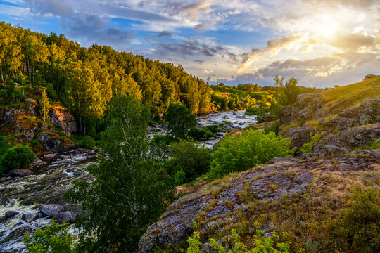 Ural Mountains. Rocks and rocky rifts on mountain river in summer. View on valley and the river Iset with rocky banks.