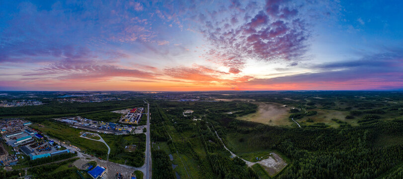 panorama of dawn in the Northern region of Russia, Khanty-Mansiysk, white nights with stunning orange dawn and clouds.