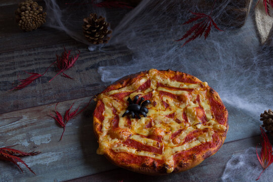 Pizza with spiderweb decoration in a dark moody and spooky background. A good start for a scary evening.
