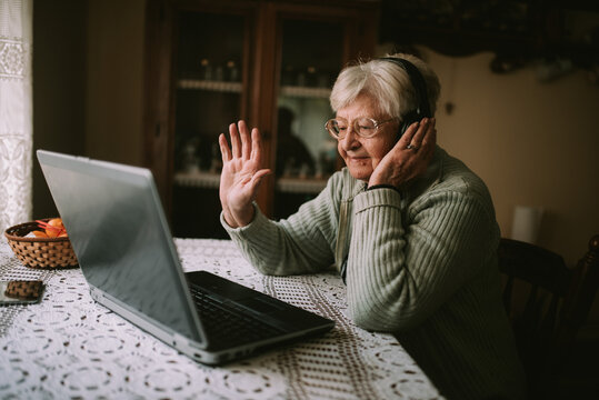 Smiling senior caucasian woman with headphones on her head sitting at a table in front of a laptop and greeting family during quarantine COVID - 19 coronavirus