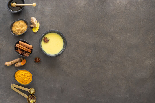 Golden Milk , Ayurvedic beverage with ingredients ginger, turmeric and other  spices on dark background. Nature  remedies for preventive illness and strong  immune system