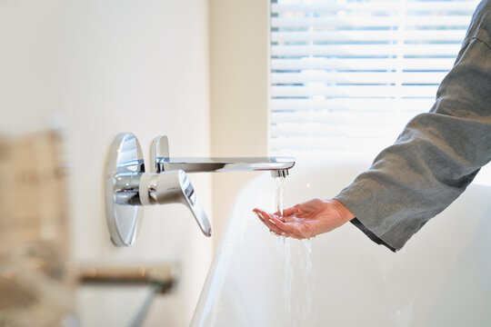 Woman checking water temperature from soaking tub faucet in bathroom