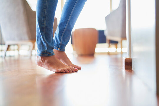 Close up bare feet of woman on hardwood floor