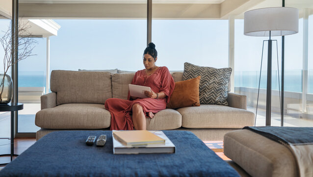 Woman relaxing with digital tablet on luxury home showcase sofa